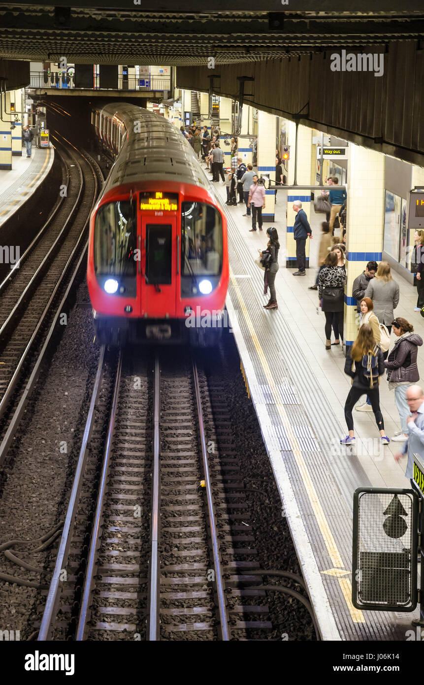A train arrives at the platform of Aldgate East London Underground Station where passengers are waiting. - Stock Image