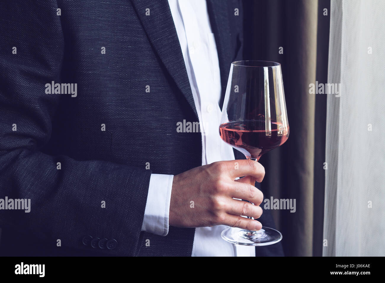 Horizontal close up of Caucasian man in black suit and white shirt holding a tall glass with rose wine  at an event - Stock Image
