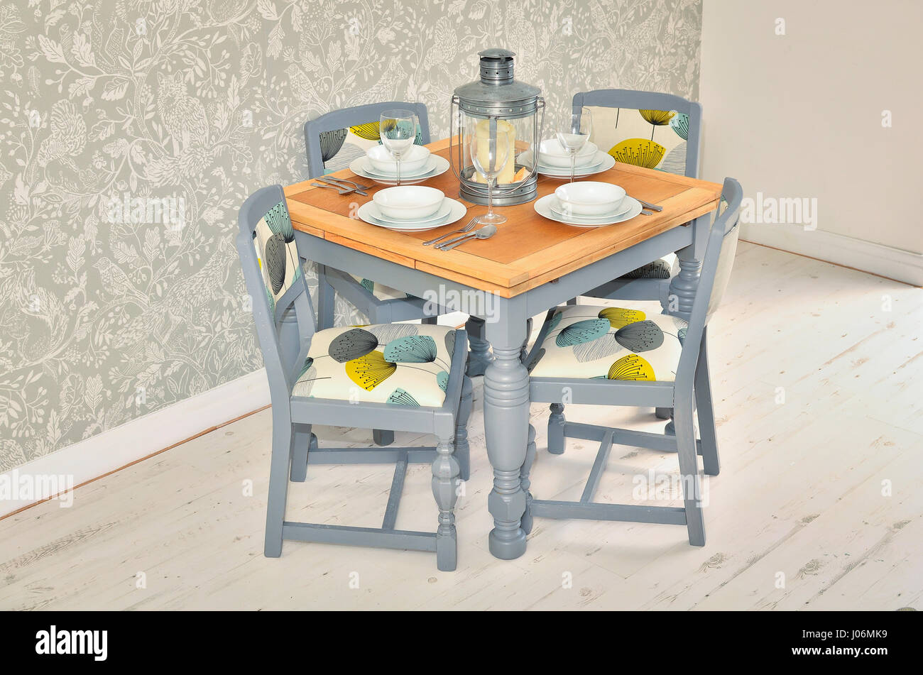 Dining table with chairs, plates, bowls and cutlery. Shabby chic dining room interior. - Stock Image