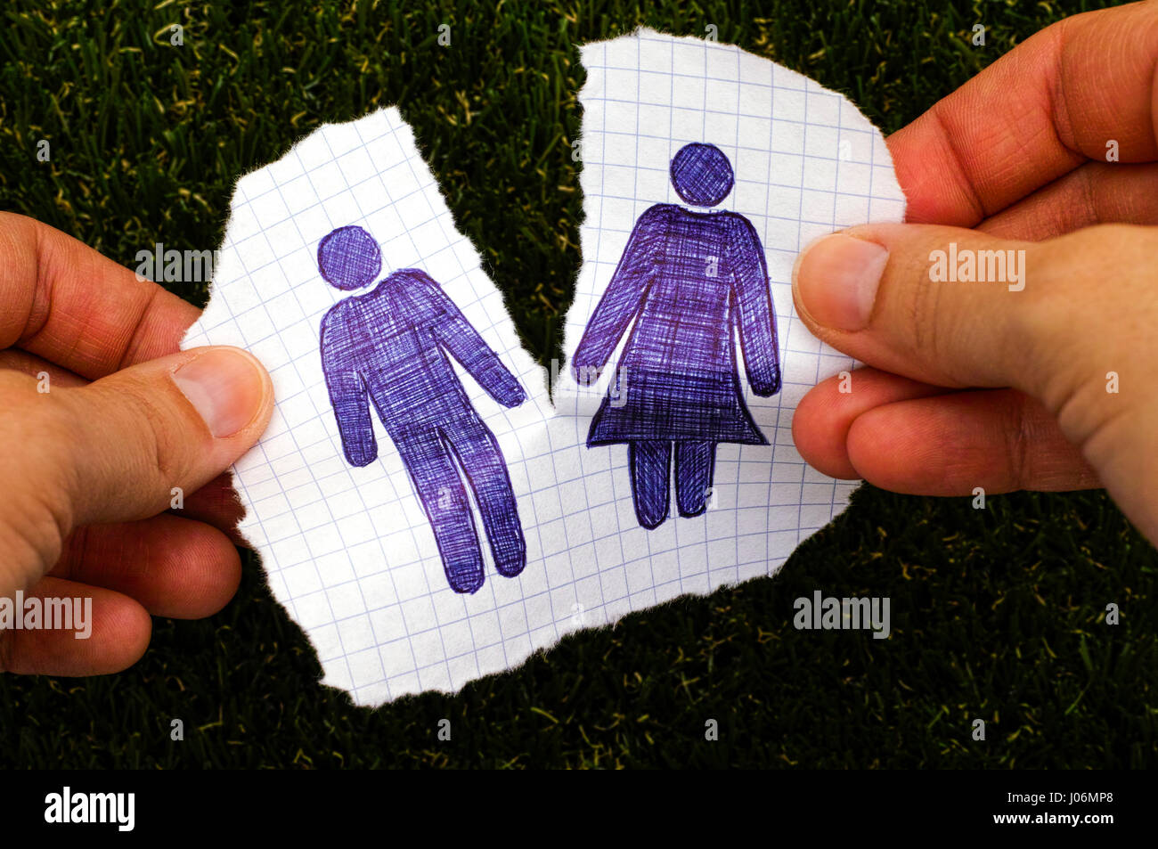 Person hands ripping piece of paper with hand drawn man and woman figures. Grass background. Doodle style. - Stock Image