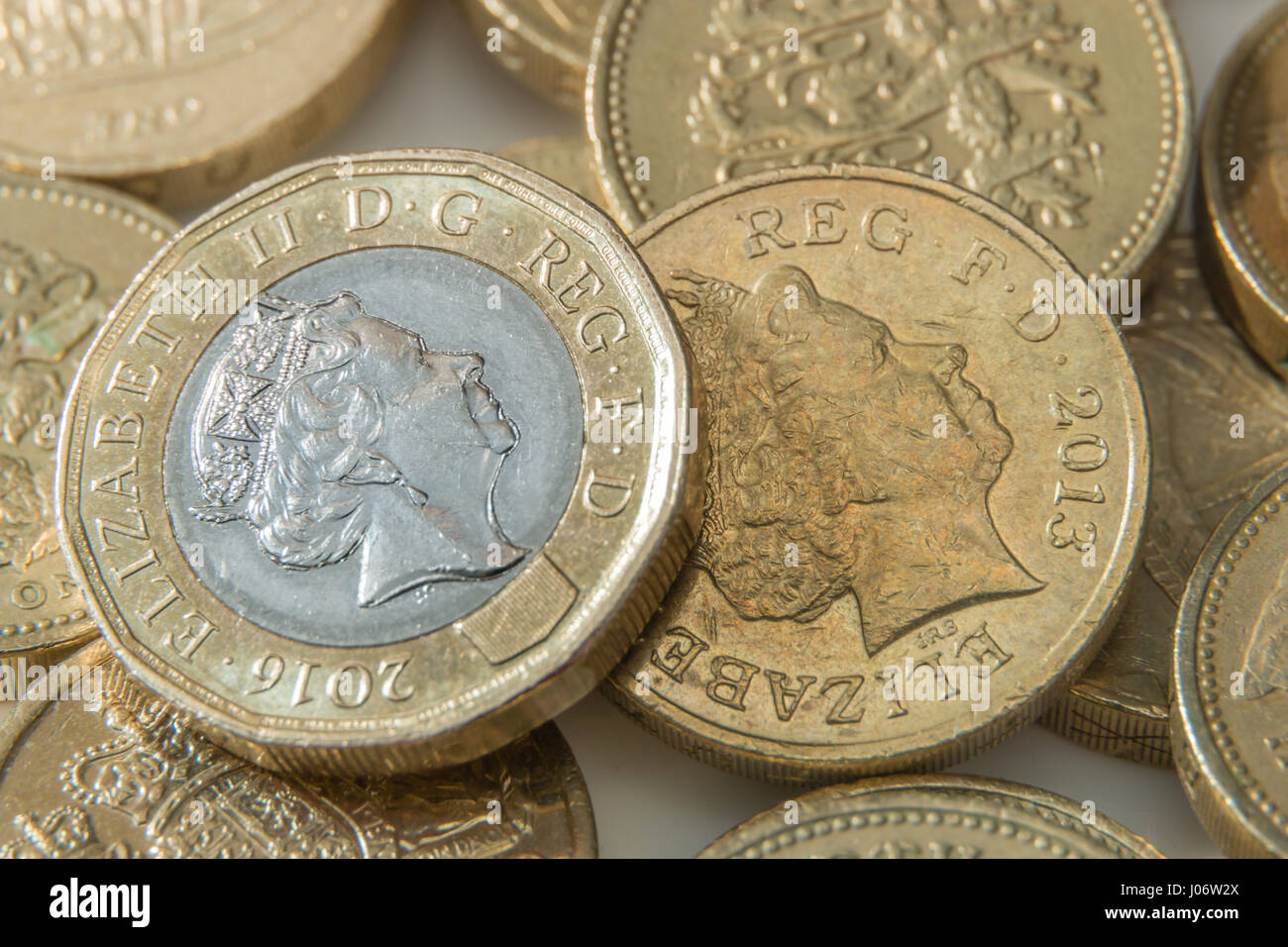 The new 12 sided British Pound Coin on top of the older round coins - Stock Image