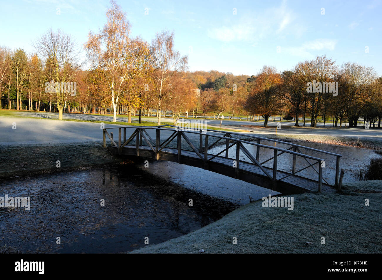 View over the frozen pond with wooden bridge on the 6th Hole, East Course,Sundridge Park Golf Club, Bromley, Kent, - Stock Image