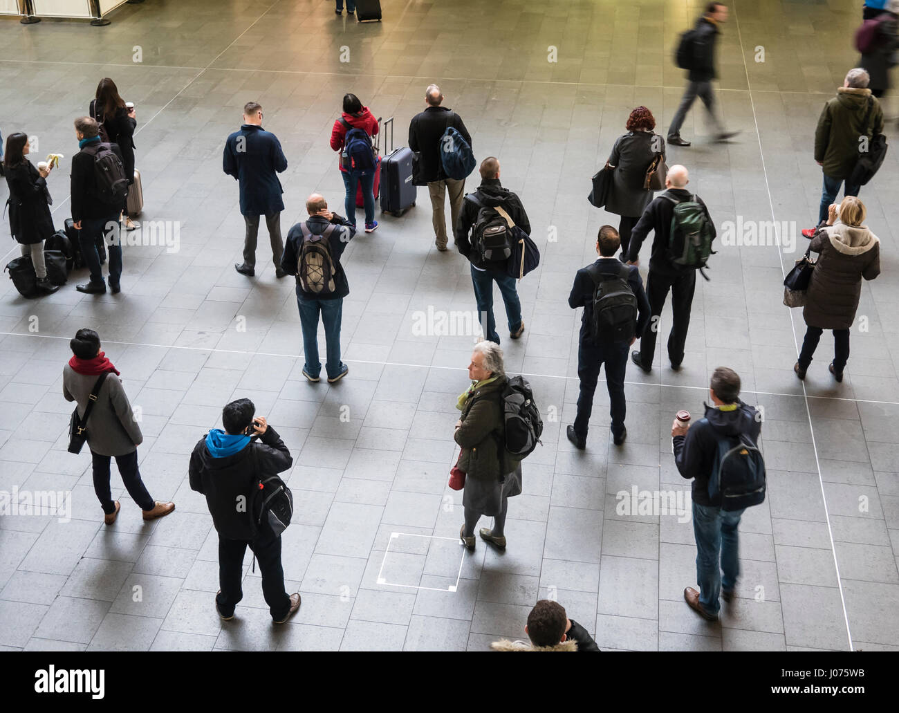 Rail Travellers Waiting for Trains at a Station in the UK - Stock Image