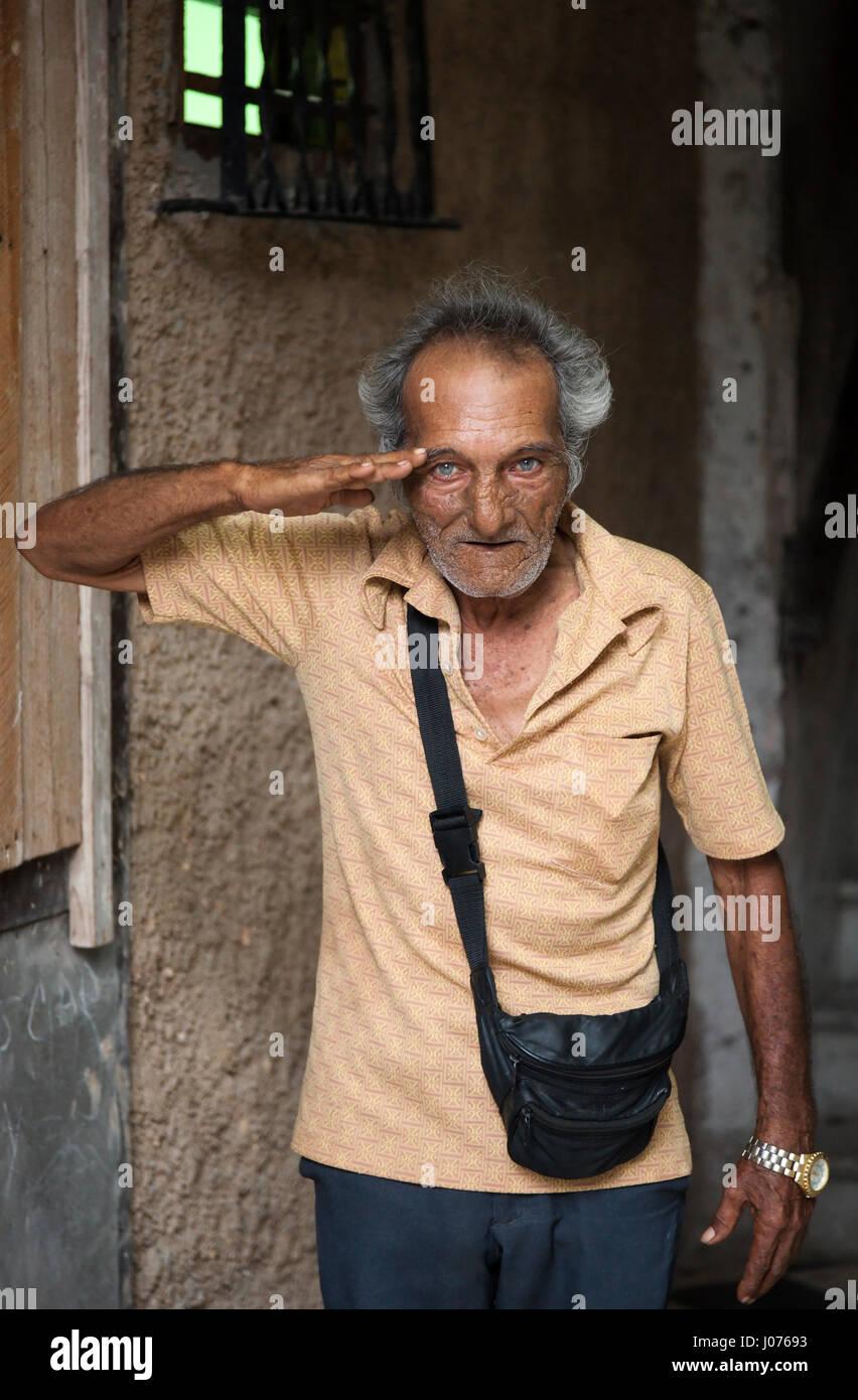 A senior citizen Cuban man saluting in Old Havana, Cuba. - Stock Image