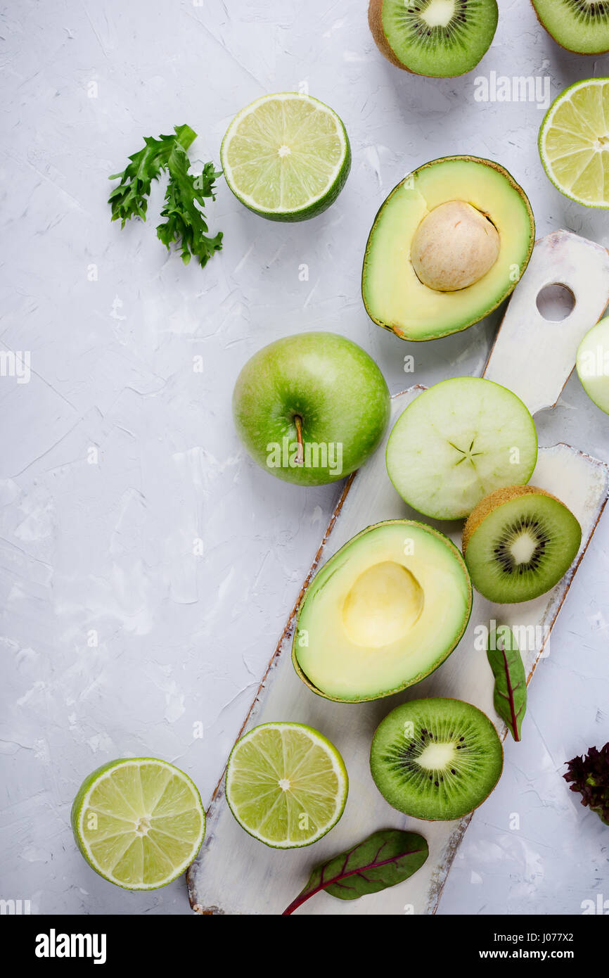 Frame of green vegetables and fruits white wooden cutting board over light gray plaster  table, food background - Stock Image