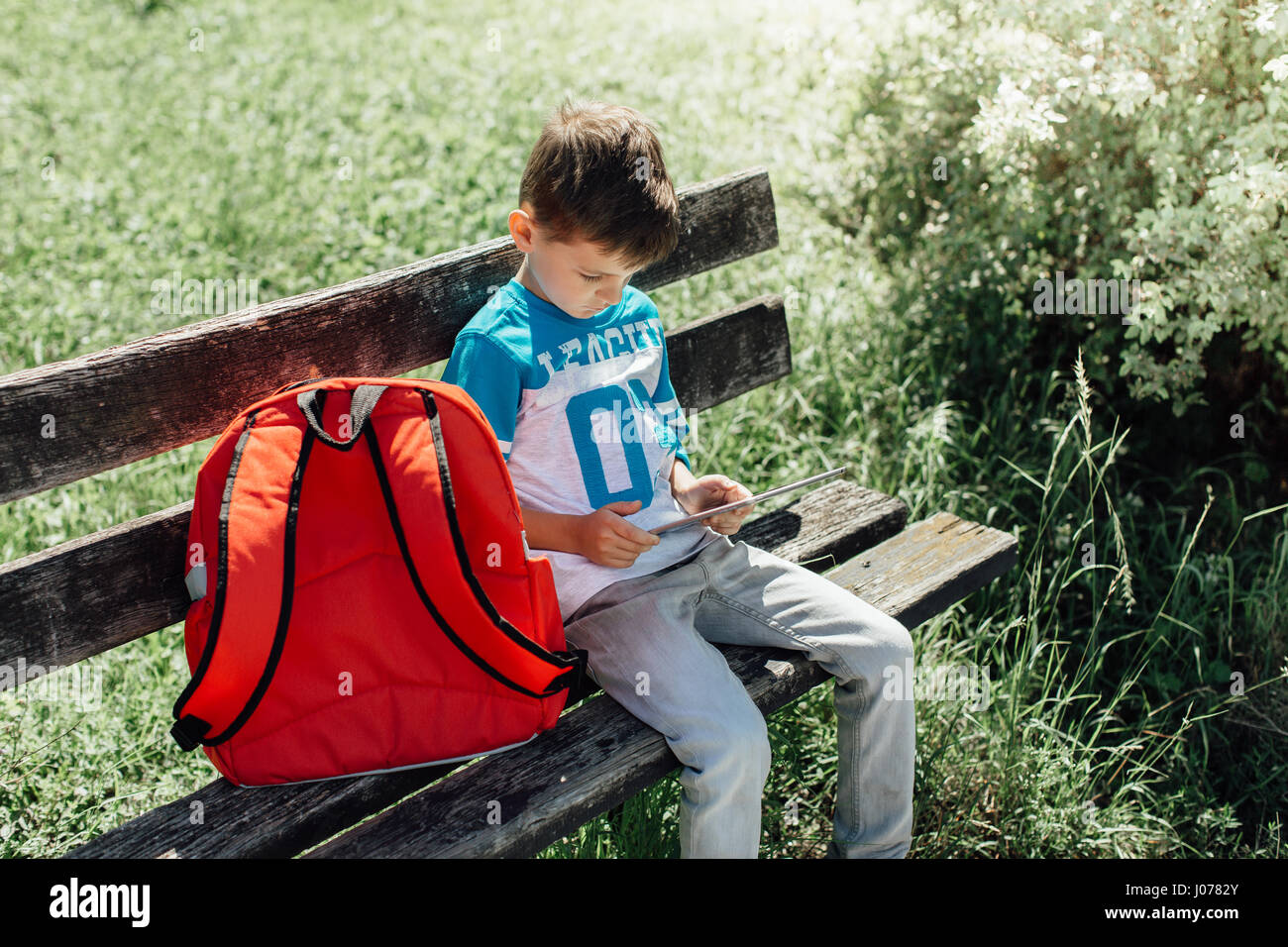 Schoolboy taking a break playing with a tablet on a bench - Stock Image
