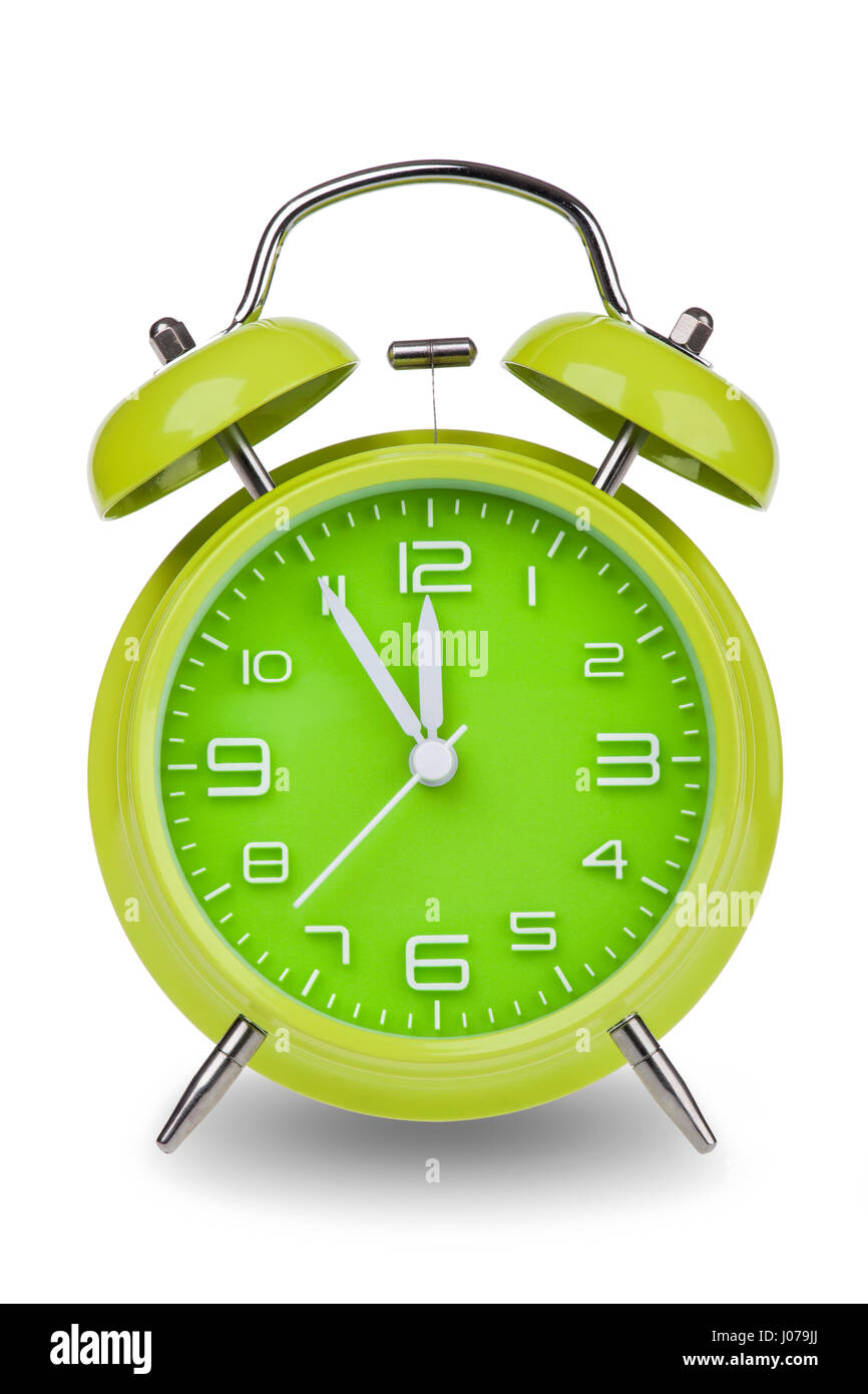 Green alarm clock with the hands at 5 minutes till 12 illustrating time is running out isolated on a white background - Stock Image