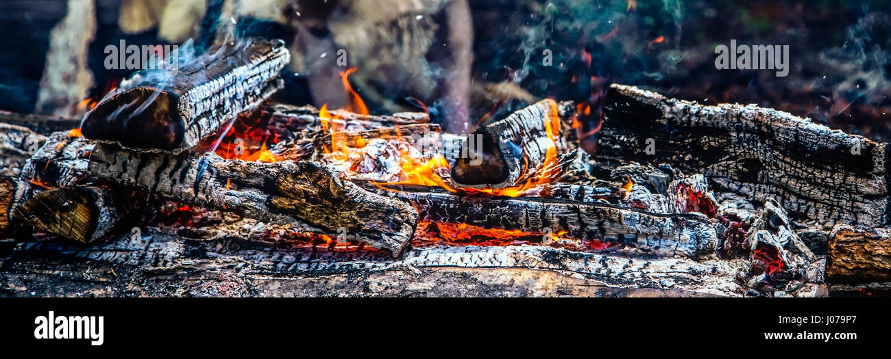 A bed of hot coals, embers, and smoke. - Stock Image