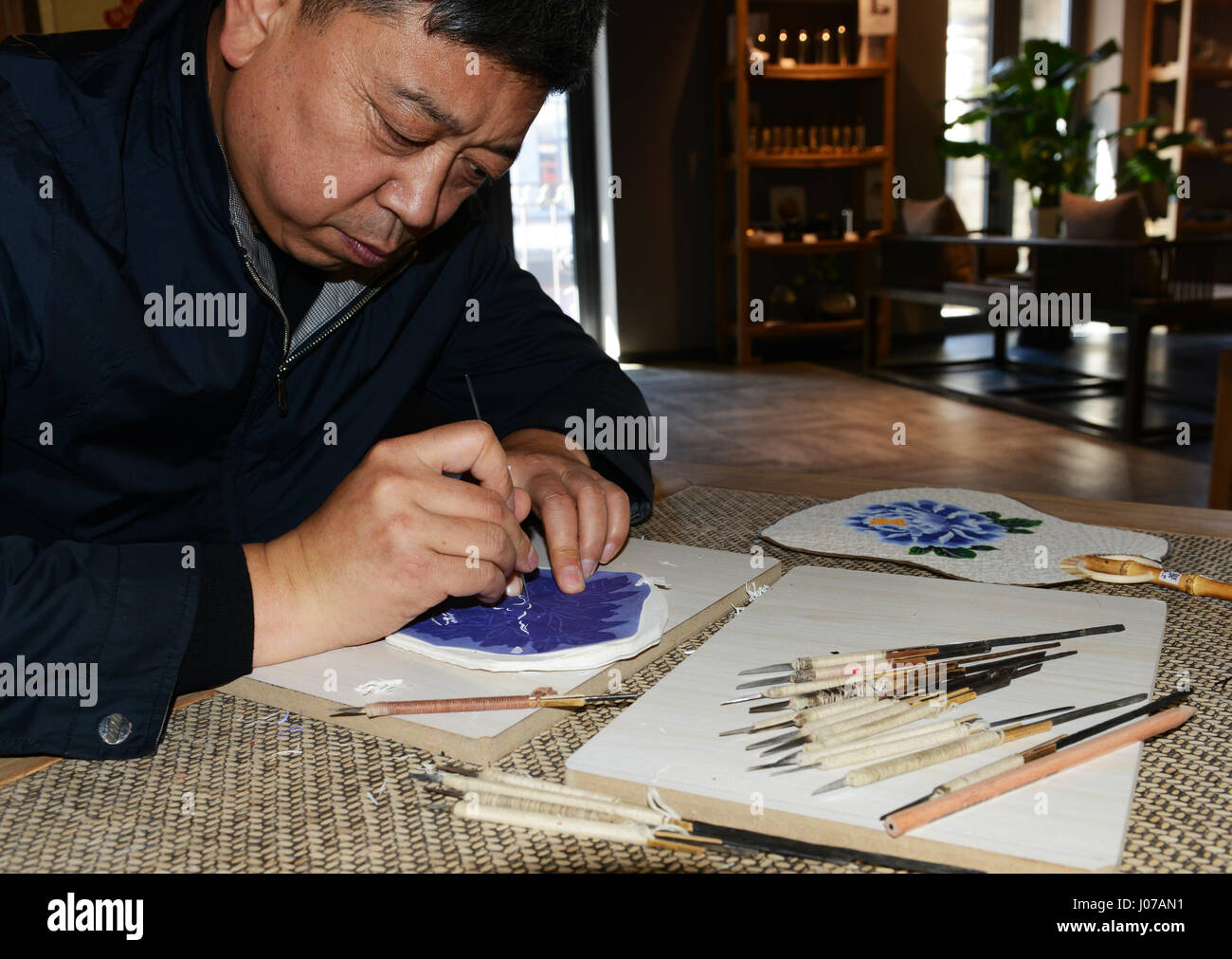 Artist Gao Dianliang working on a traditional Chinese paper-cut art ( jianzhi) using a tiny set of knives. - Stock Image