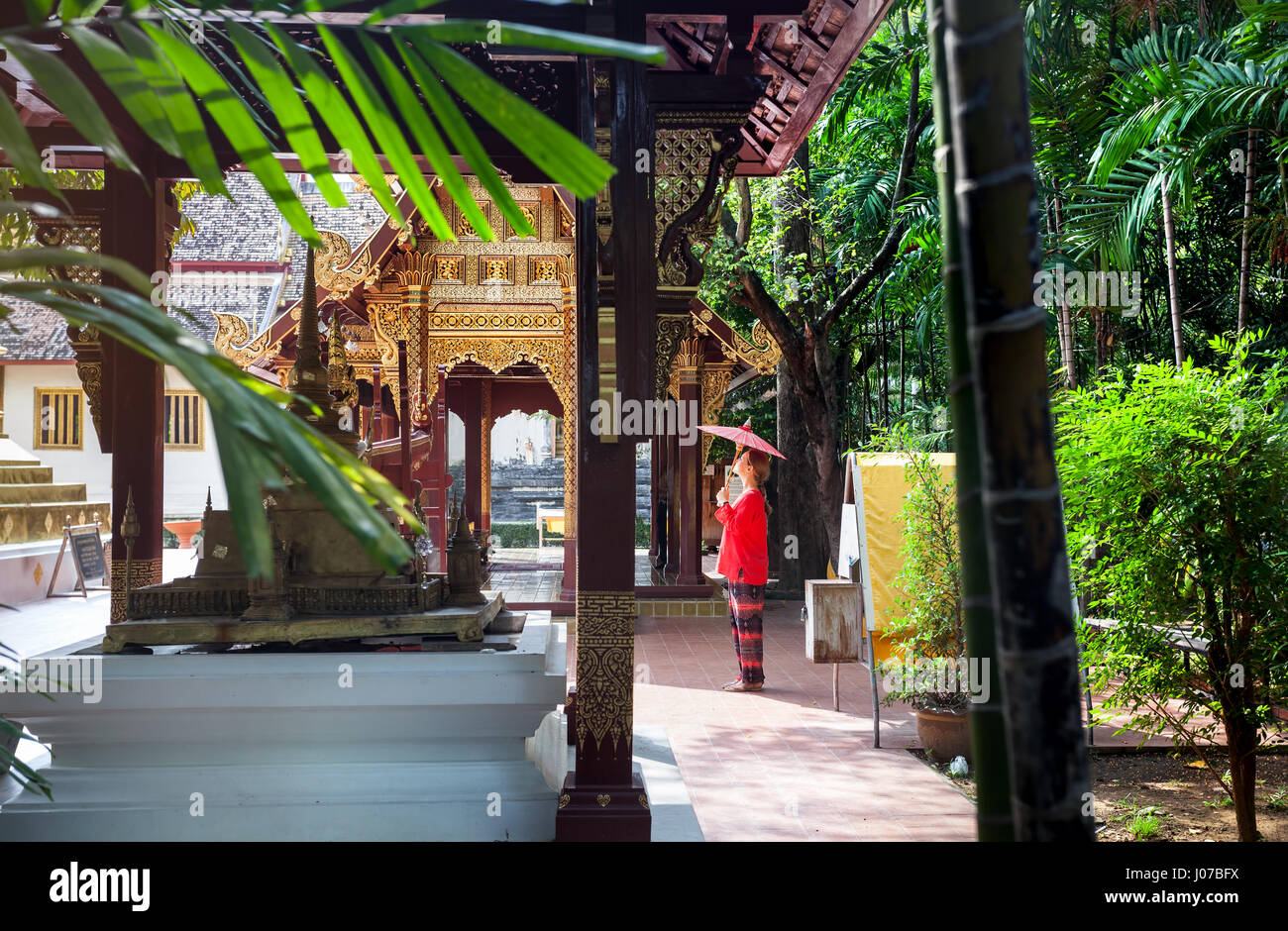 Woman tourist with red traditional Thai umbrella near Golden temple Wat Phra Singh in Chiang Mai, Thailand Stock Photo