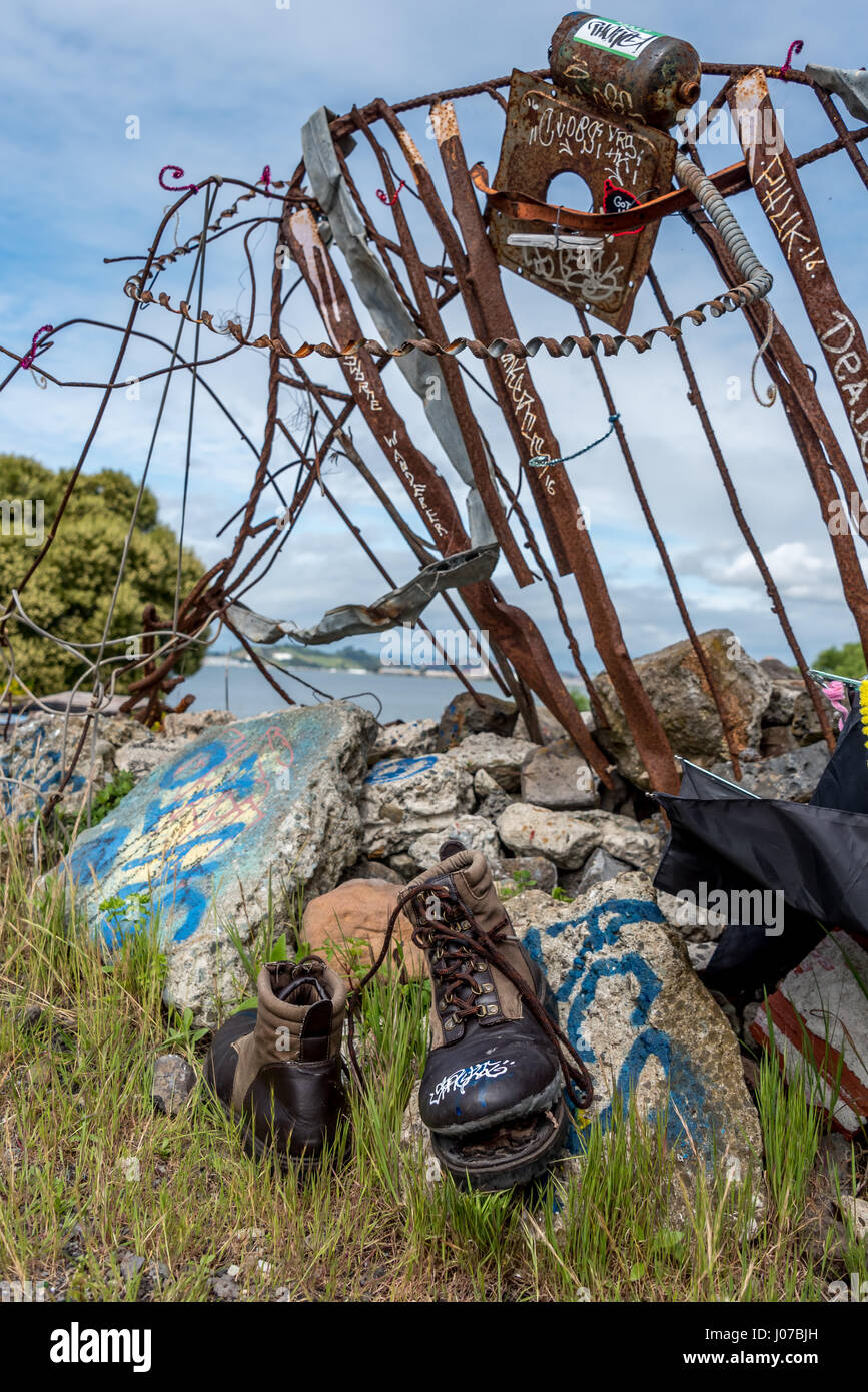 An abandoned pair of hiking boots with blown-out sole rest in peace a the former junkyard / garbage dump by San - Stock Image