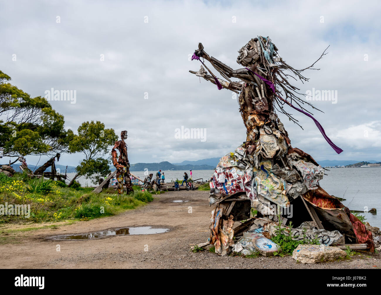 Large, dramatic outdoor sculpture of woman made from driftwood and upcycled garbage beside San Francisco Bay - Stock Image