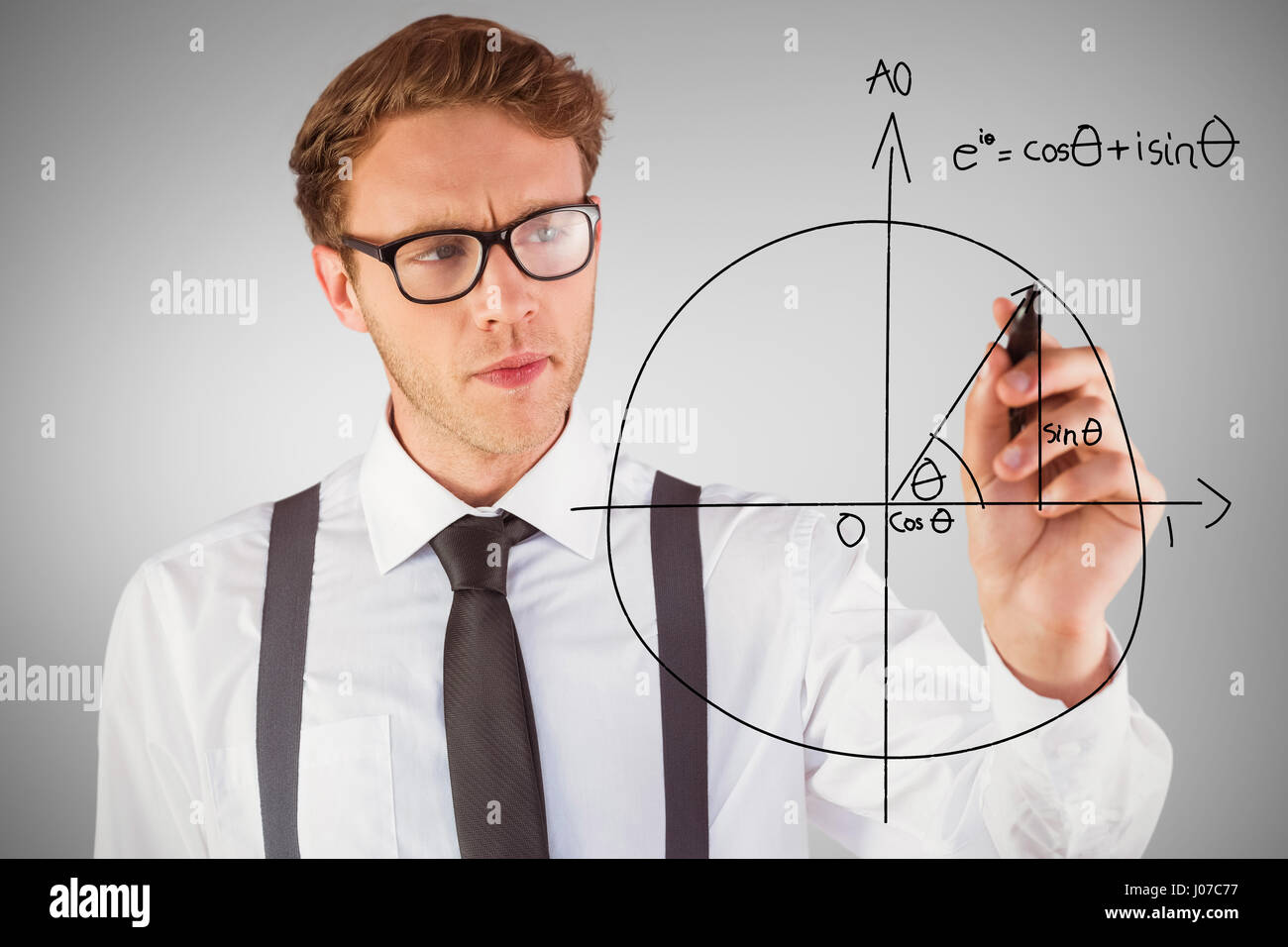 Geeky businessman writing with marker against grey vignette - Stock Image