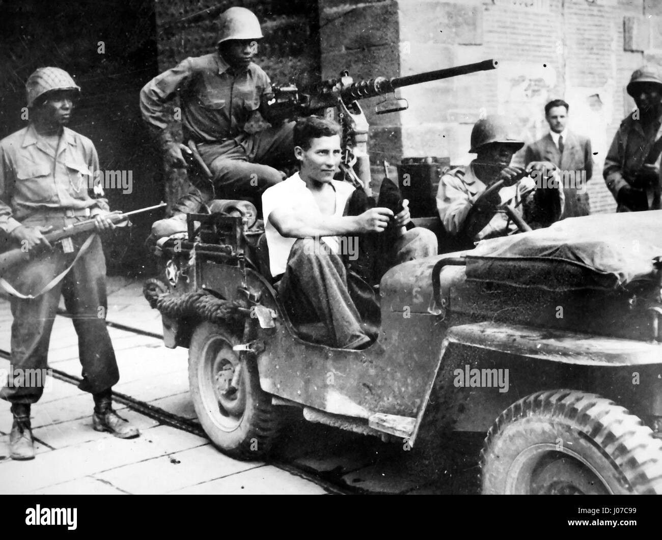 'Tricky Nazi captured. German prisoner wearing civilian clothes, sits in jeep at south gate of walled city of - Stock Image