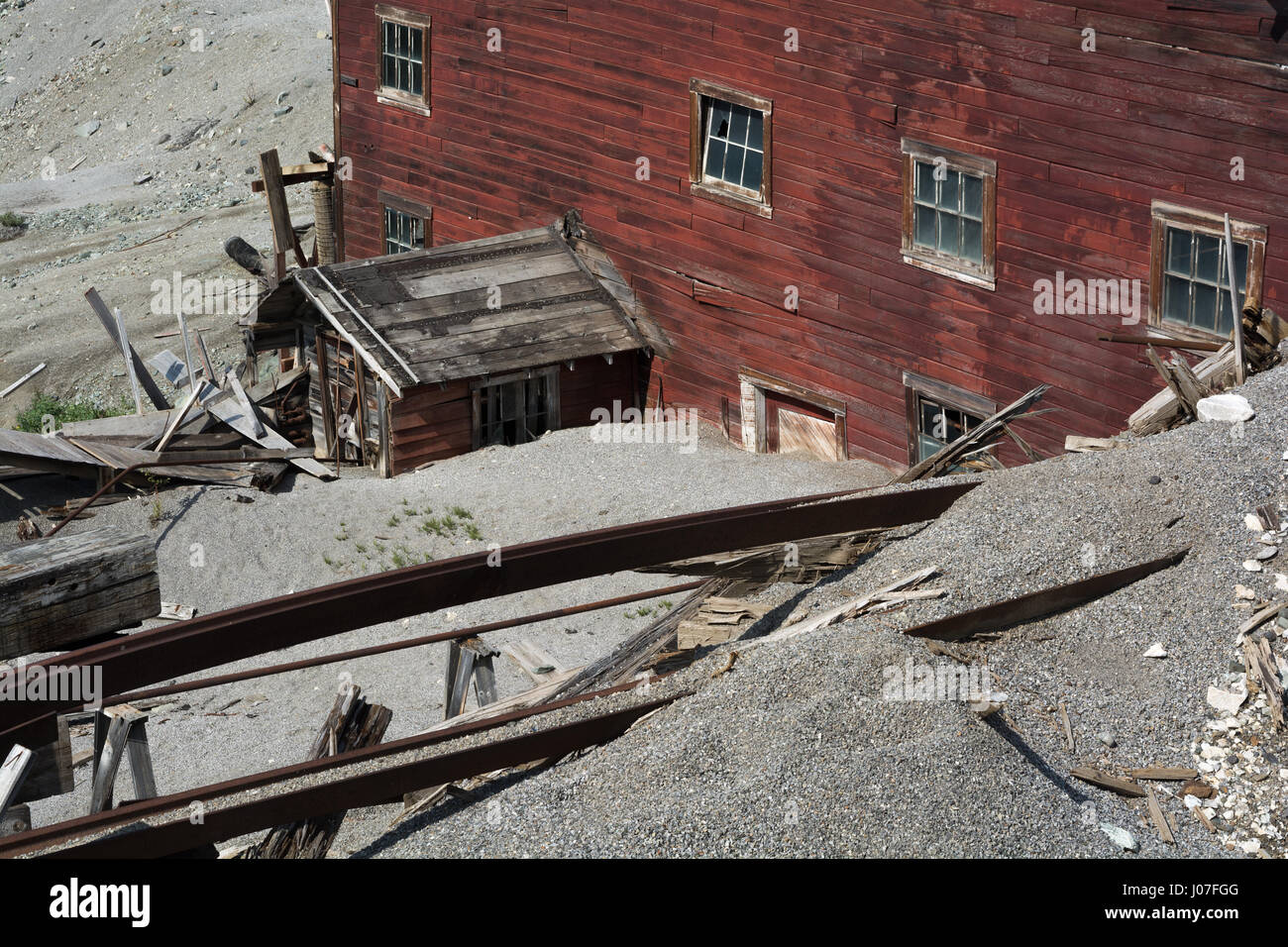 A hundred years of weather has edoded the side of a hill on which a multistory red building is slowly decaying. - Stock Image