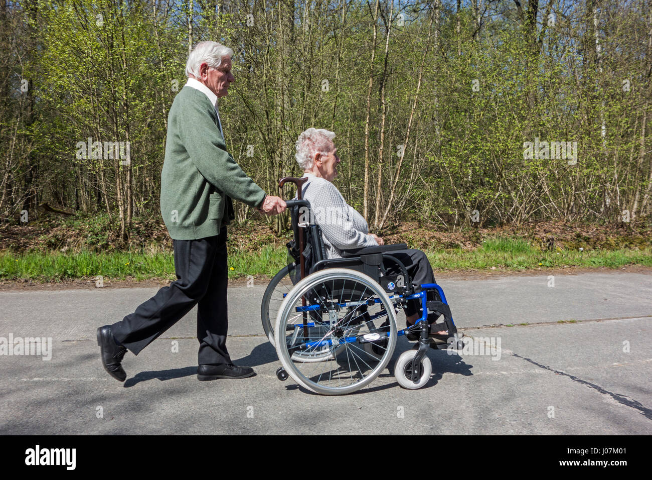 Retired husband taking disabled elderly wife in wheelchair for a walk in the park on a sunny day in spring - Stock Image