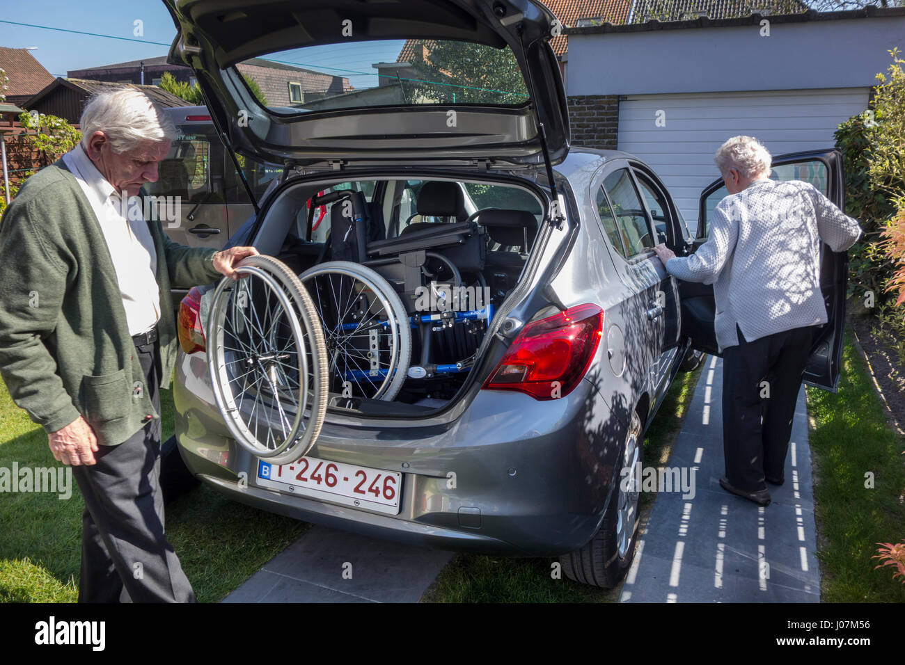 Senior husband fitting dismantled wheelchair from physically disabled elderly wife in car trunk at home before going - Stock Image