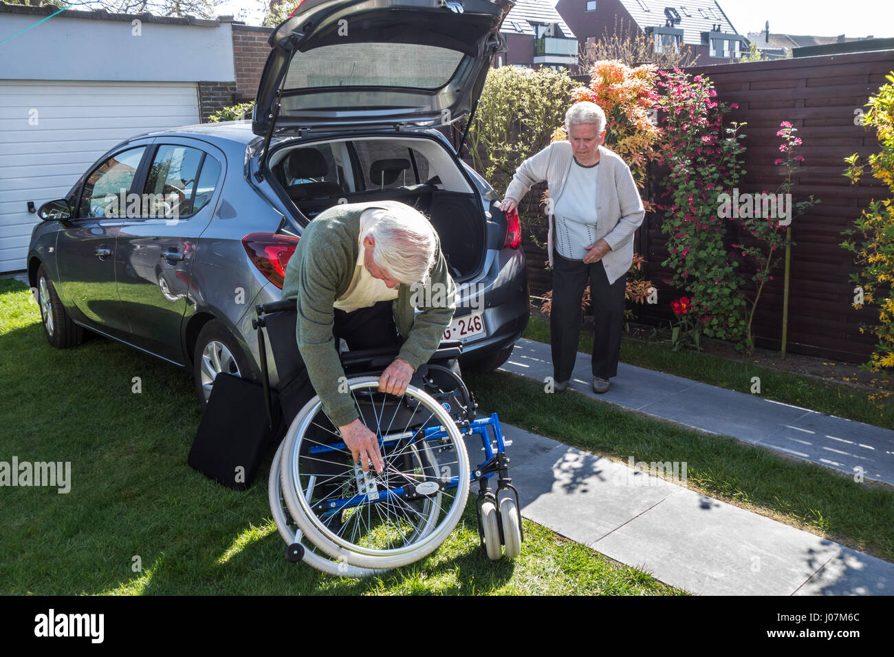 Senior husband assembling wheelchair from physically disabled elderly wife in front of car after returning at home - Stock Image
