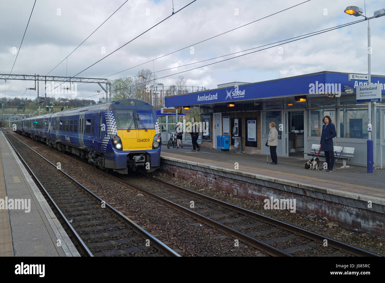 Anniesland railway station train arriving with perspective and passengers - Stock Image