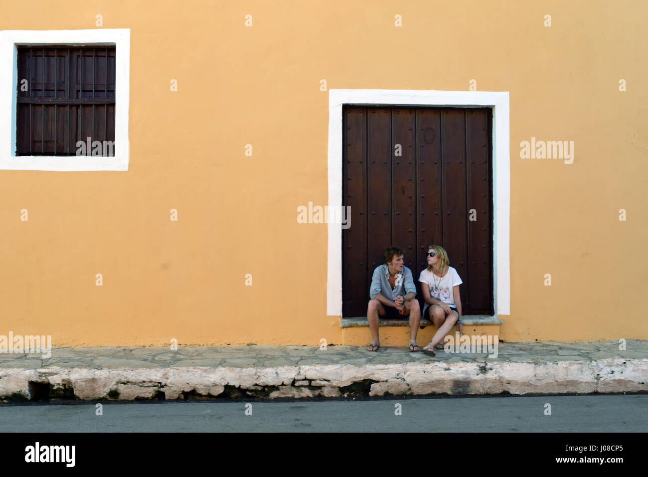 Couple sitting in front of a colonial house in Remedios, Cuba - Stock Image