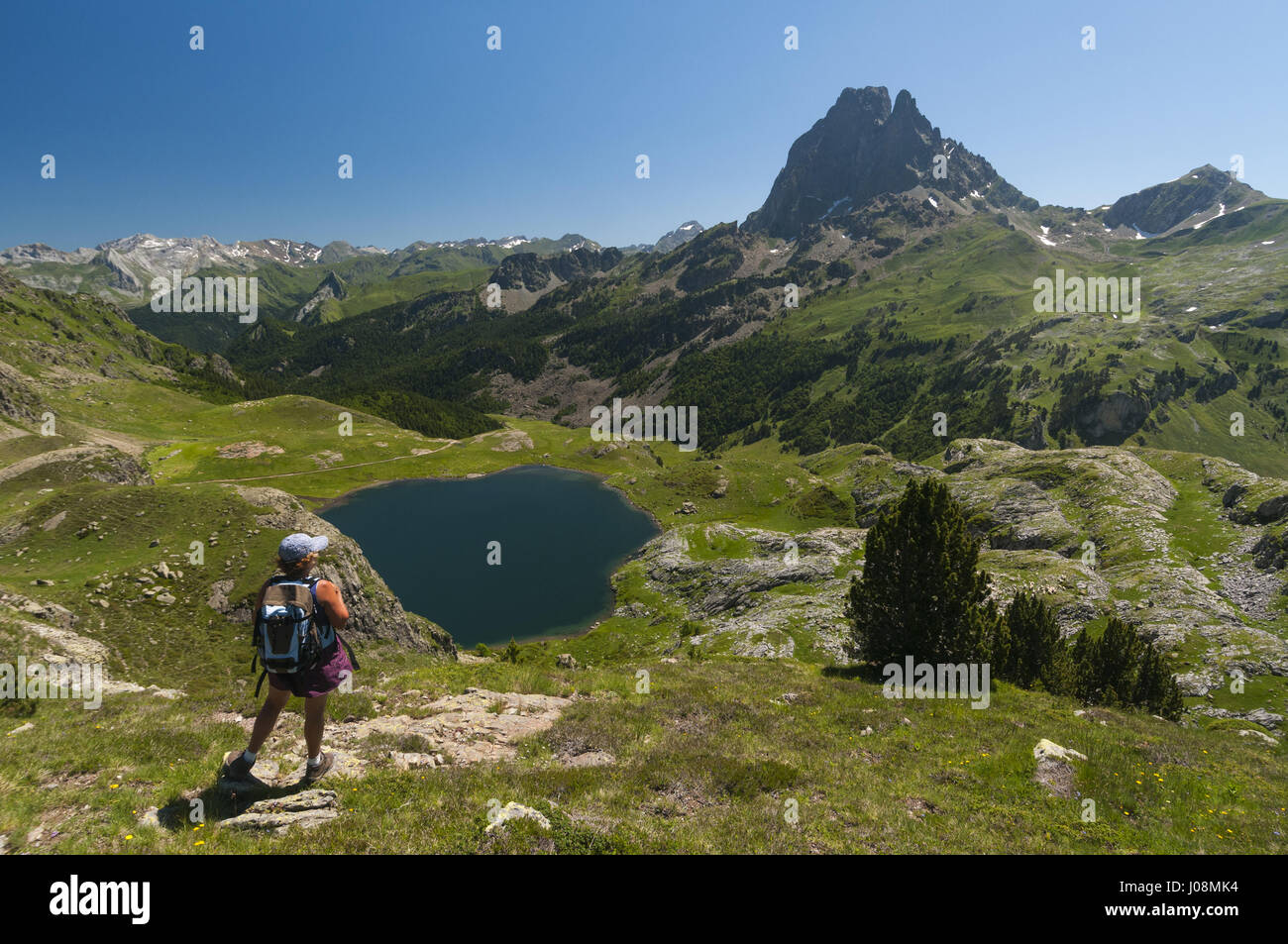 France, Pyrenees, Lacs d'Ayous lakes, Lake Roumassot with Pic du Midi d'Ossau and hiker - Stock Image