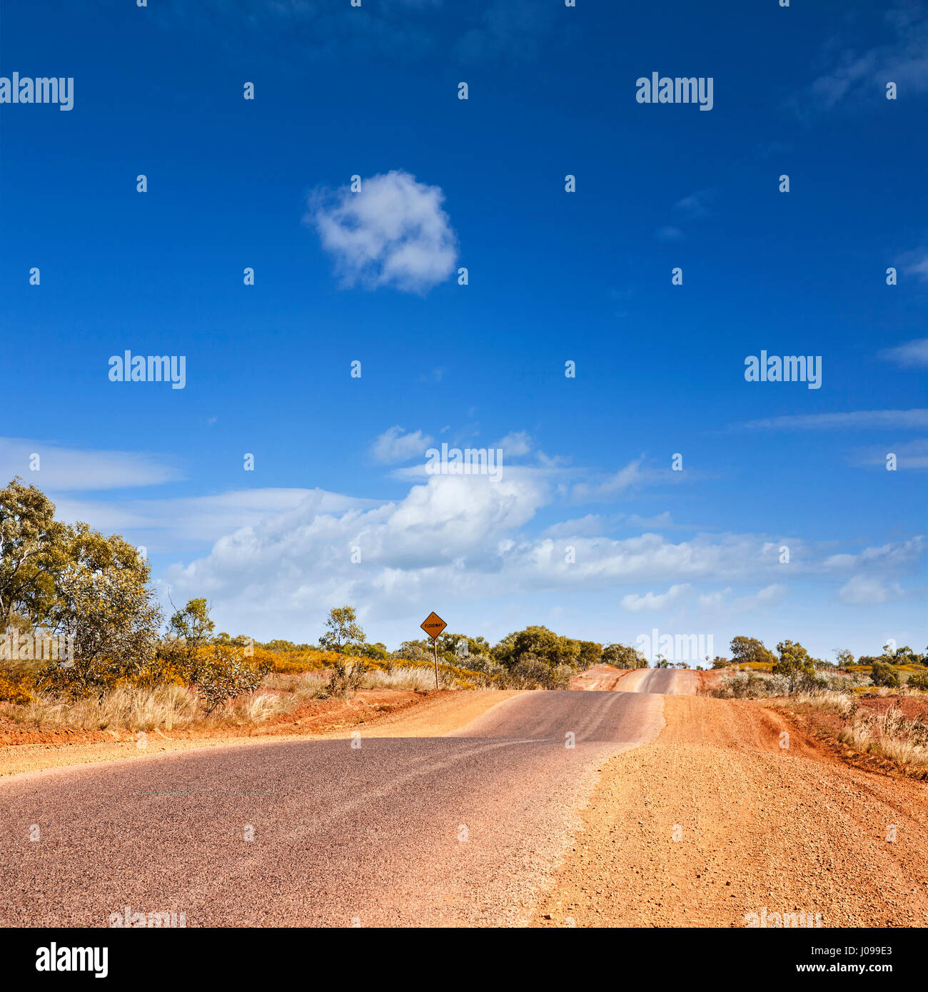 This bumpy road in the desert is the Barkly Highway in outback Queensland Australia. - Stock Image