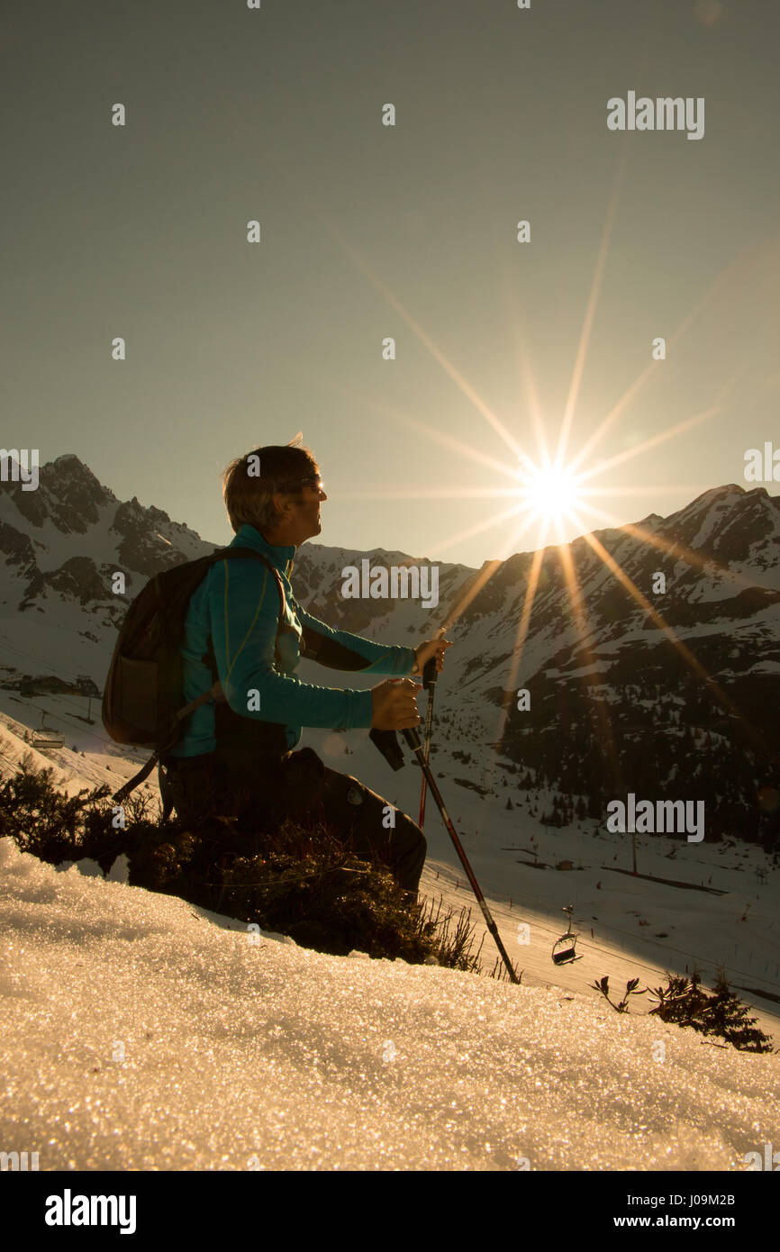 Nordic Walking as the sun sets hiking with backpack and poles rambler in the mountains and in the snow at sunset, - Stock Image