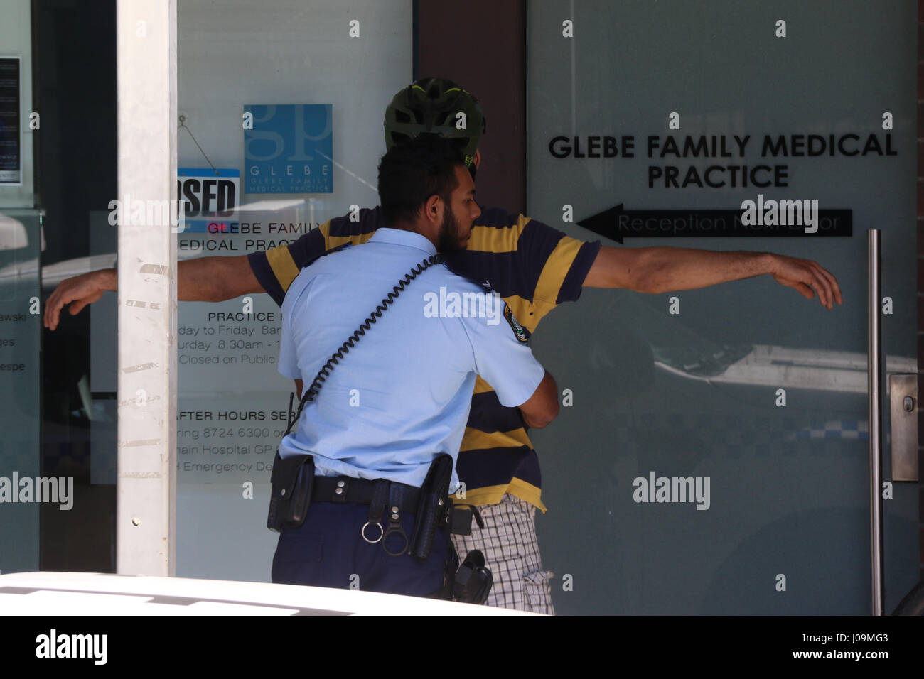 Police stop and search a cyclist on Glebe Point Road, Glebe, inner-west Sydney, Australia. - Stock Image