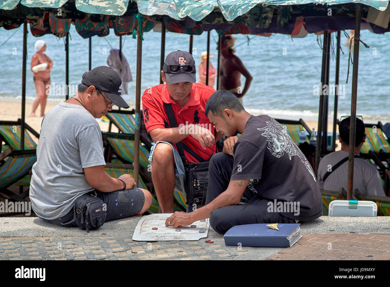 Thailand men playing draughts or checkers using a paper board and bottle tops as pieces. Stock Photo