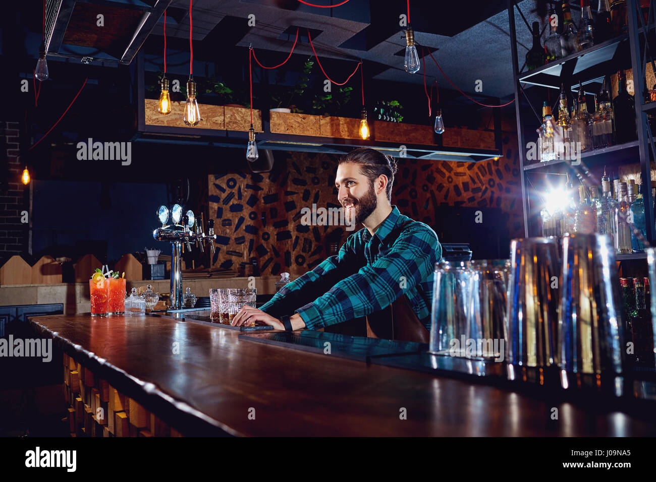 The bartender smiles at  workplace in  bar - Stock Image