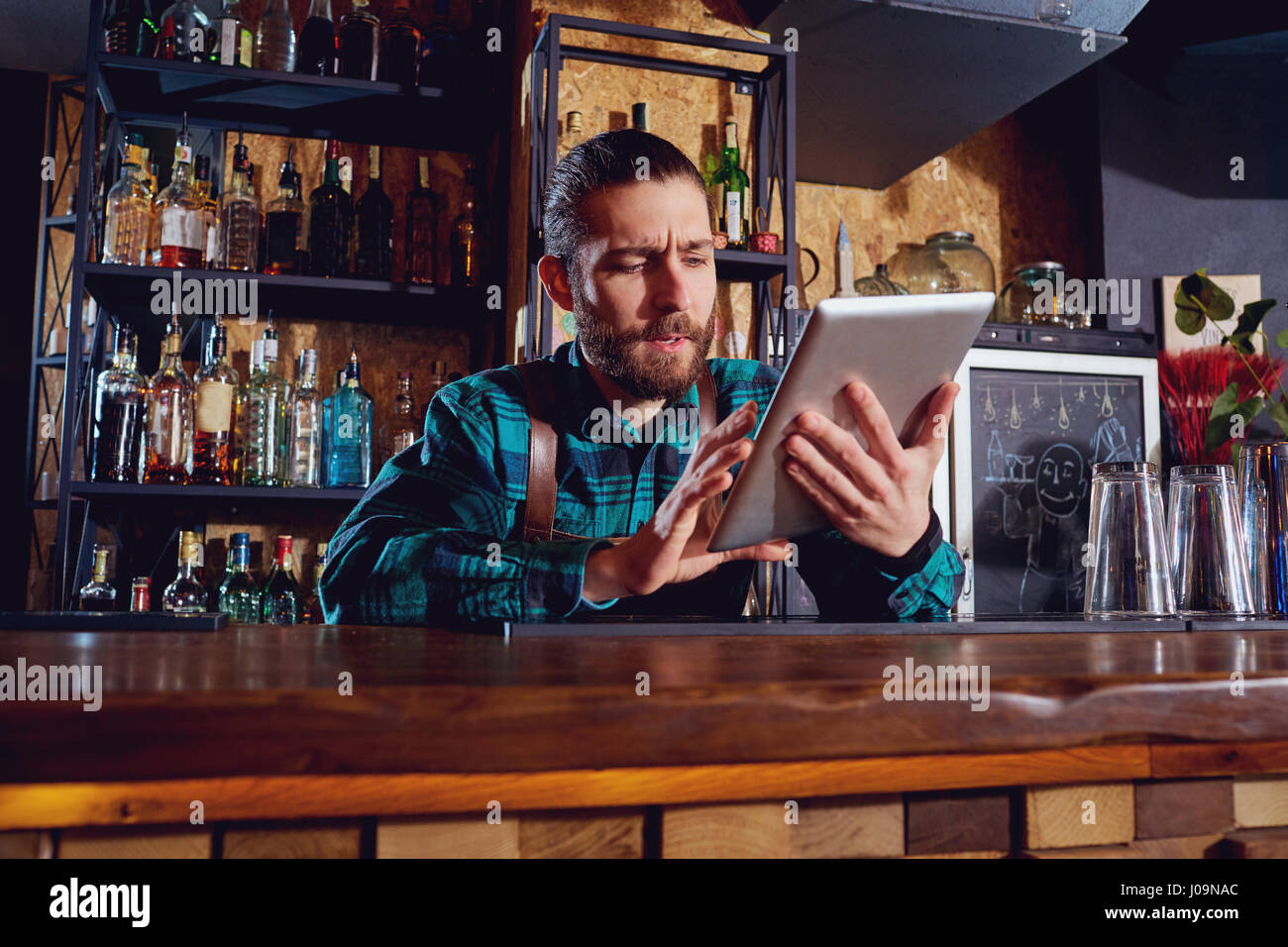 Waiters, bartenders barista work with the tablet in cafe bar res - Stock Image