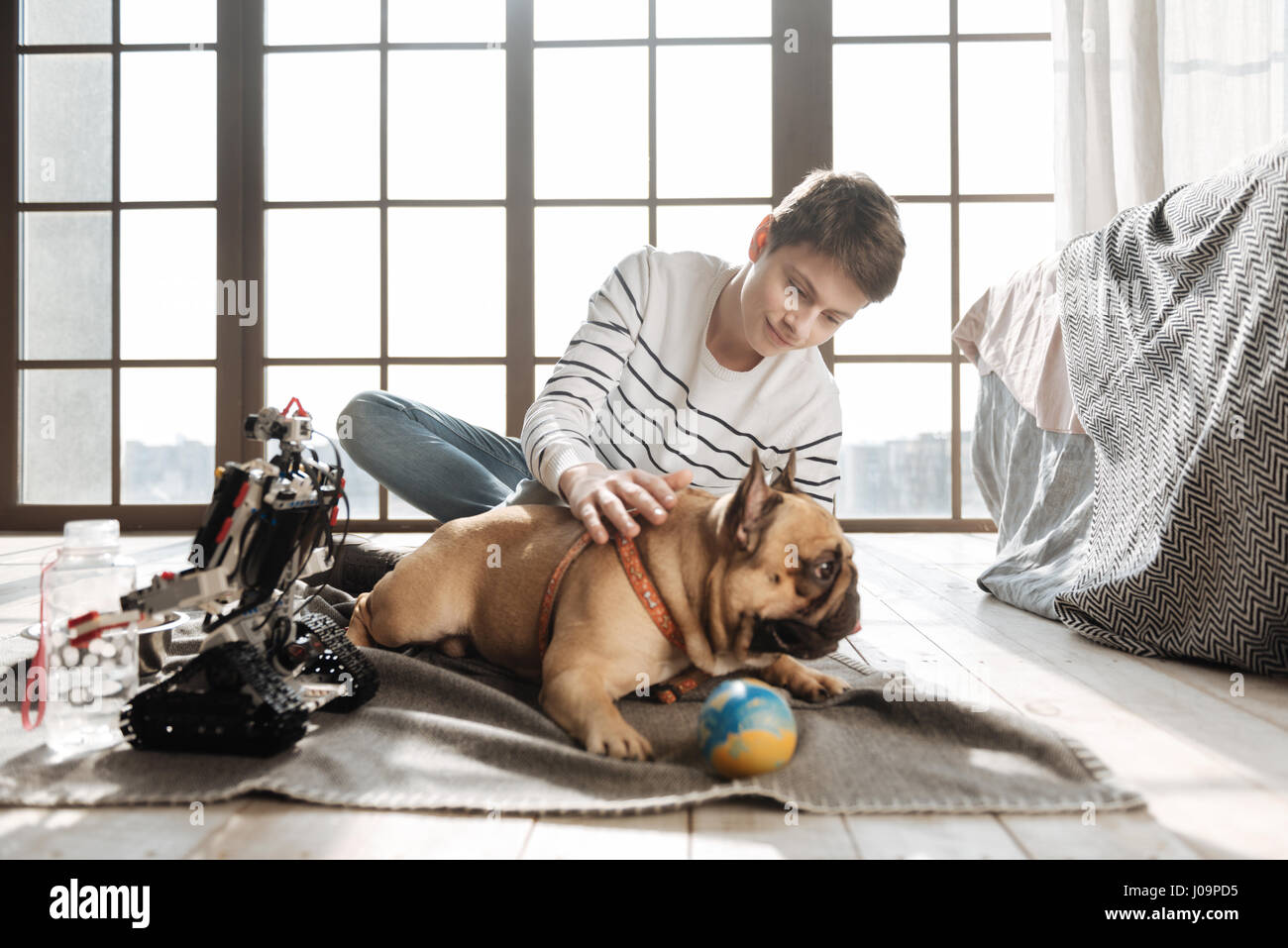 Obedient pet. Attractive man-child sitting behind his dog on the floor smiling and staring at him - Stock Image