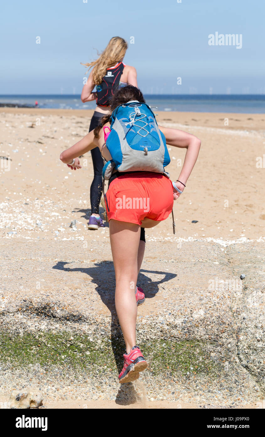 Young woman achieves the goal while running on the beach in Margate, Kent, England - Stock Image