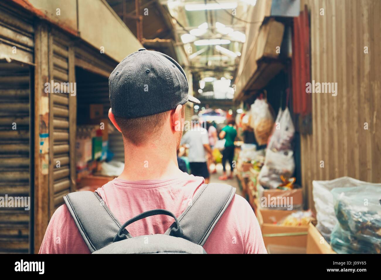 Young traveler with backpack in street market in Chinatown - Kuala Lumpur, Malaysia - Stock Image