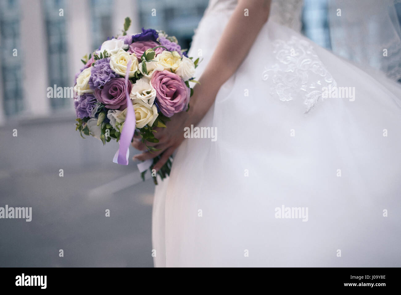 A Wedding Bouquet Of Purple And White Flowers In The Hands Of The