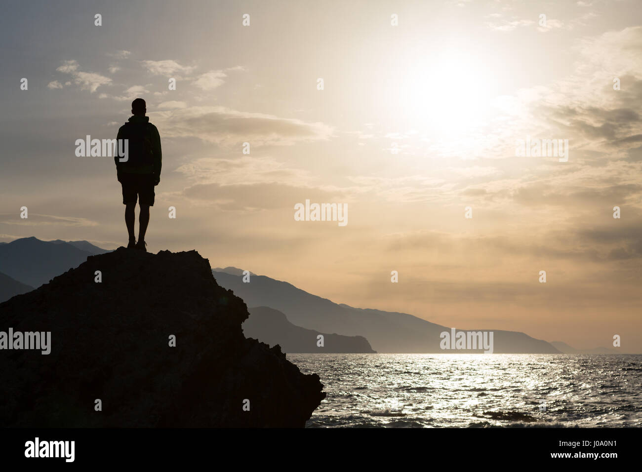 Hiker or runner silhouette backpacker, man looking at inspirational ocean landscape and islands on mountain peak. - Stock Image