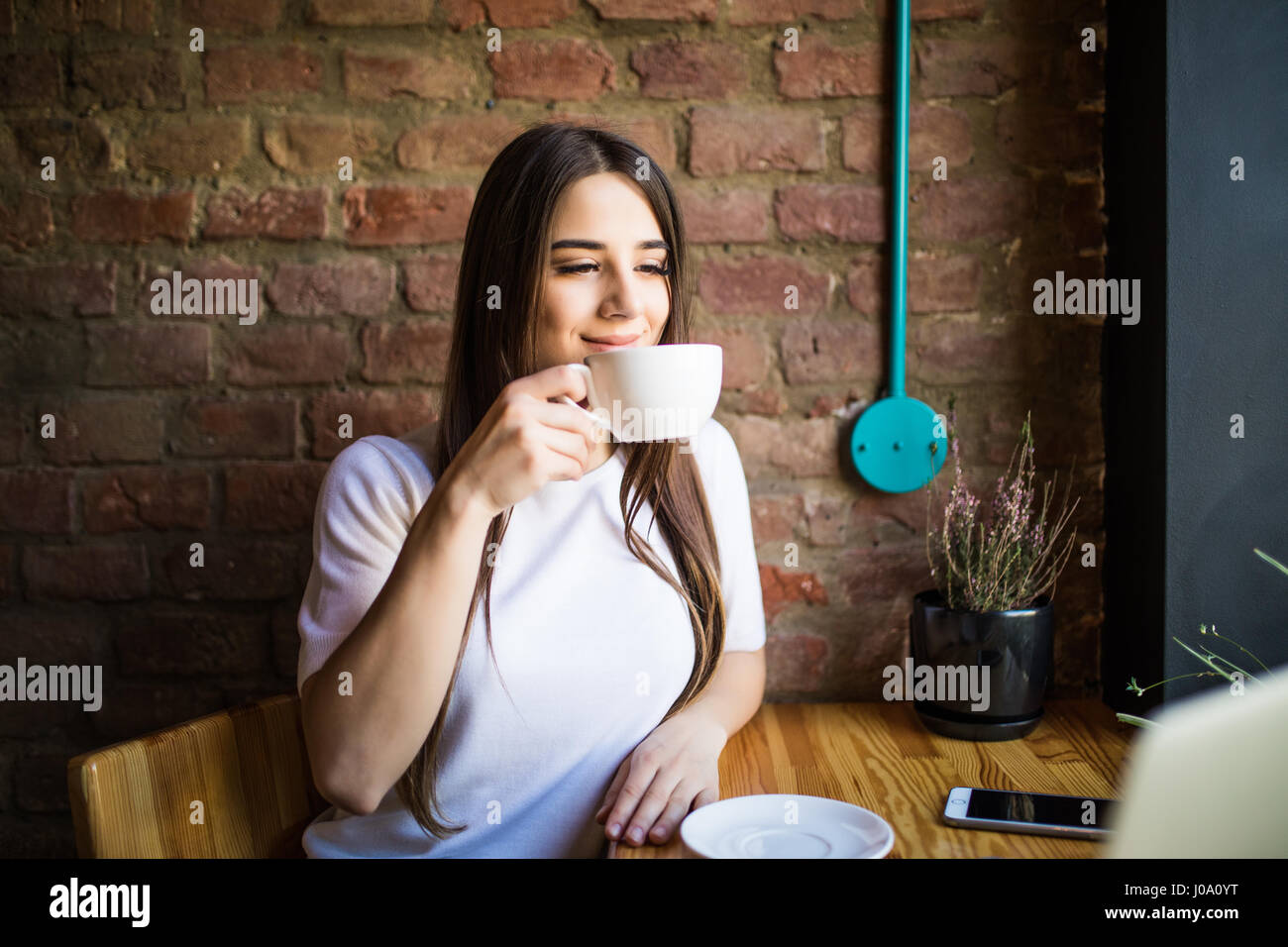 Portrait of young gorgeous female drinking tea and looking with smile out of the coffee shop window while enjoying - Stock Image
