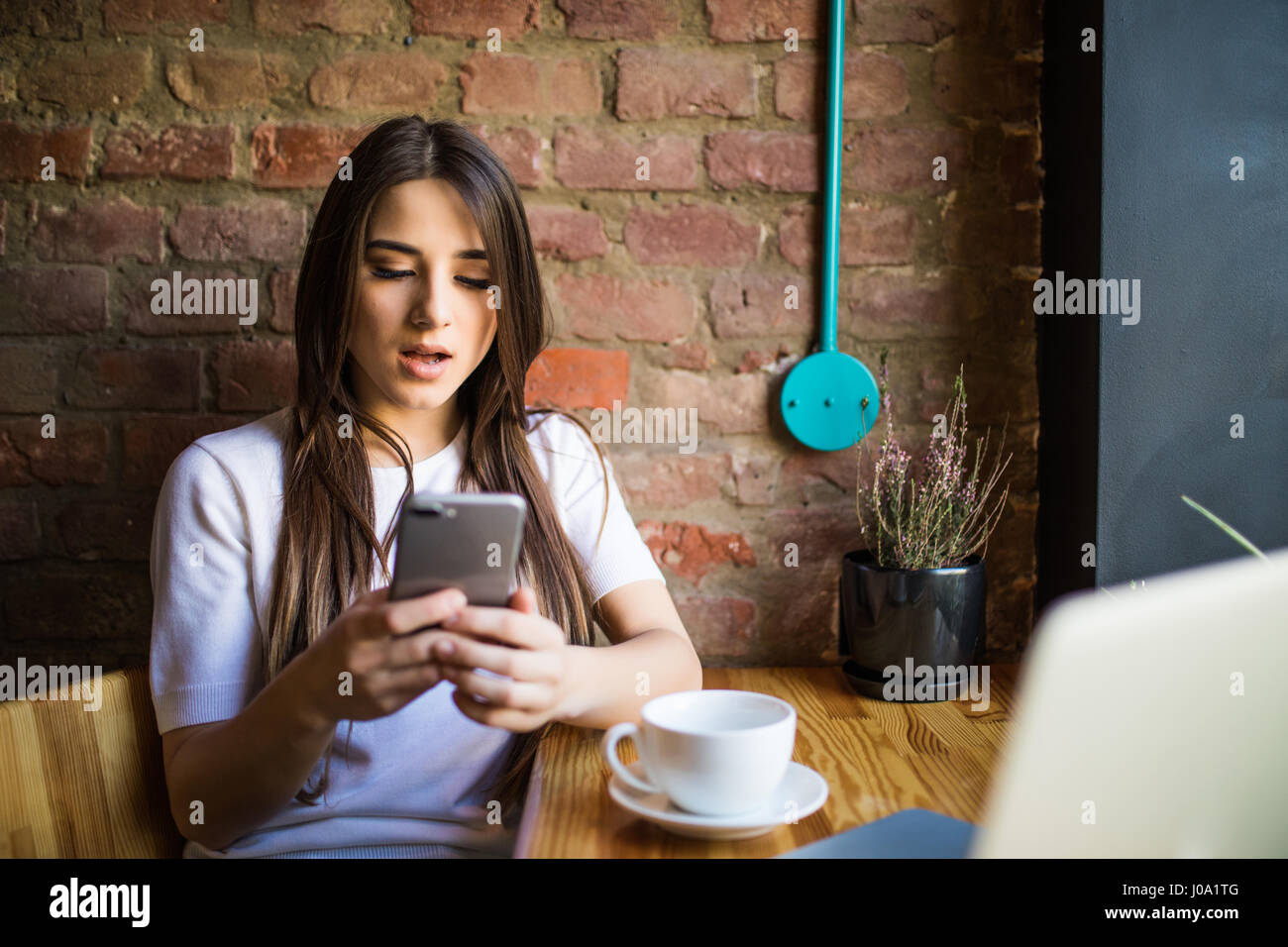 Woman typing write message on smart phone in a modern cafe. Young pretty girl sitting at a table with coffee or - Stock Image