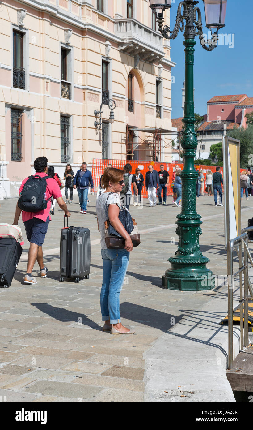 VENICE, ITALY - SEPTEMBER 22, 2016: Unrecognized tourists near Ferrovia water bus station. Venice is situated across - Stock Image