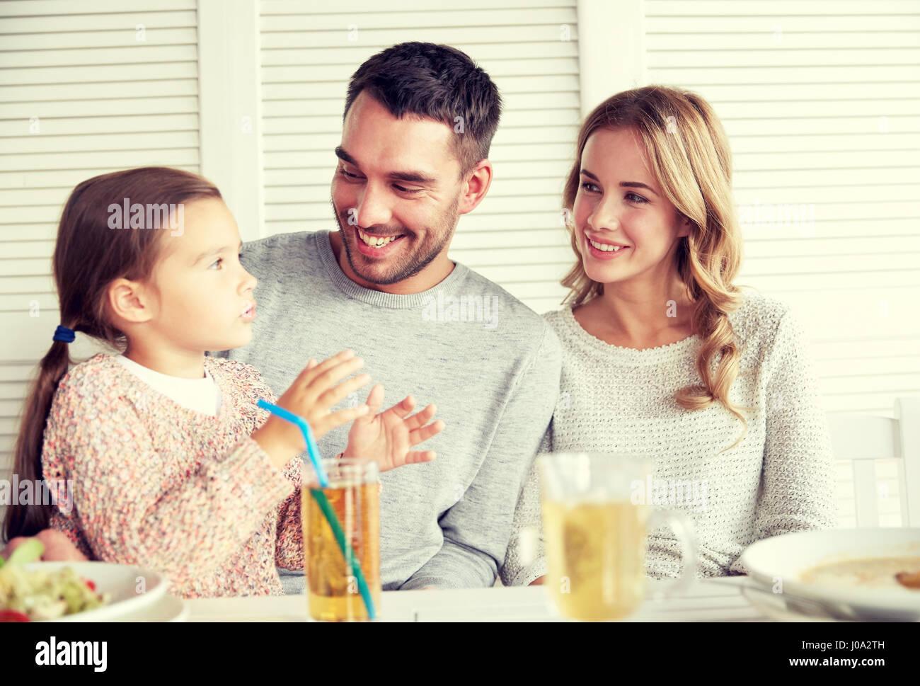 happy family having dinner at restaurant or cafe - Stock Image