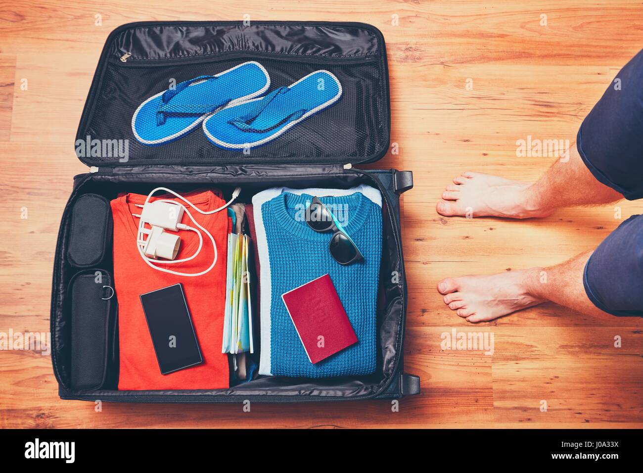 preparing for the trip young man packing vacation items mobile
