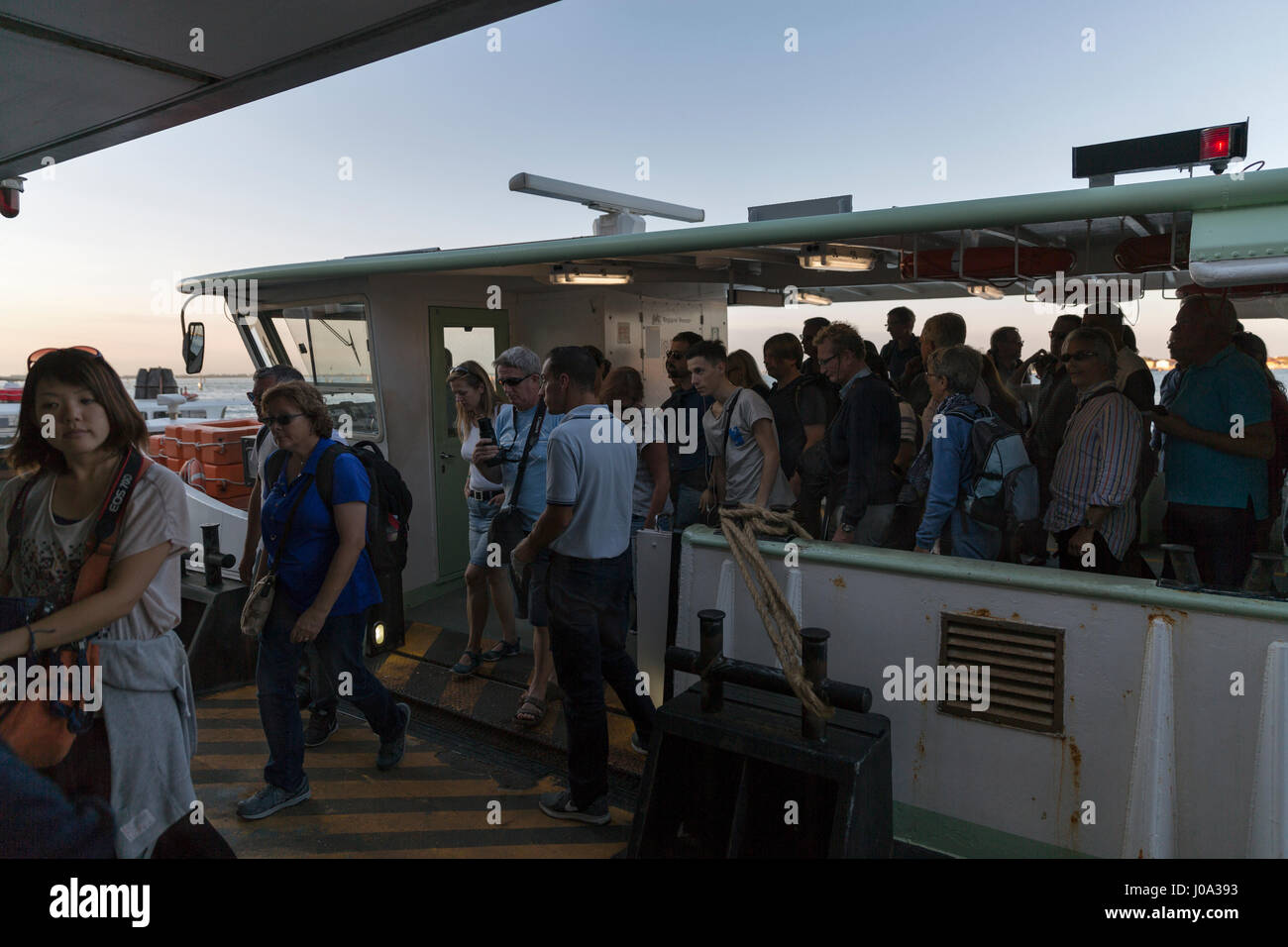 VENICE, ITALY - SEPTEMBER 22, 2016: Unrecognized tourists leaving the water bus at sunset. Venice is situated across - Stock Image