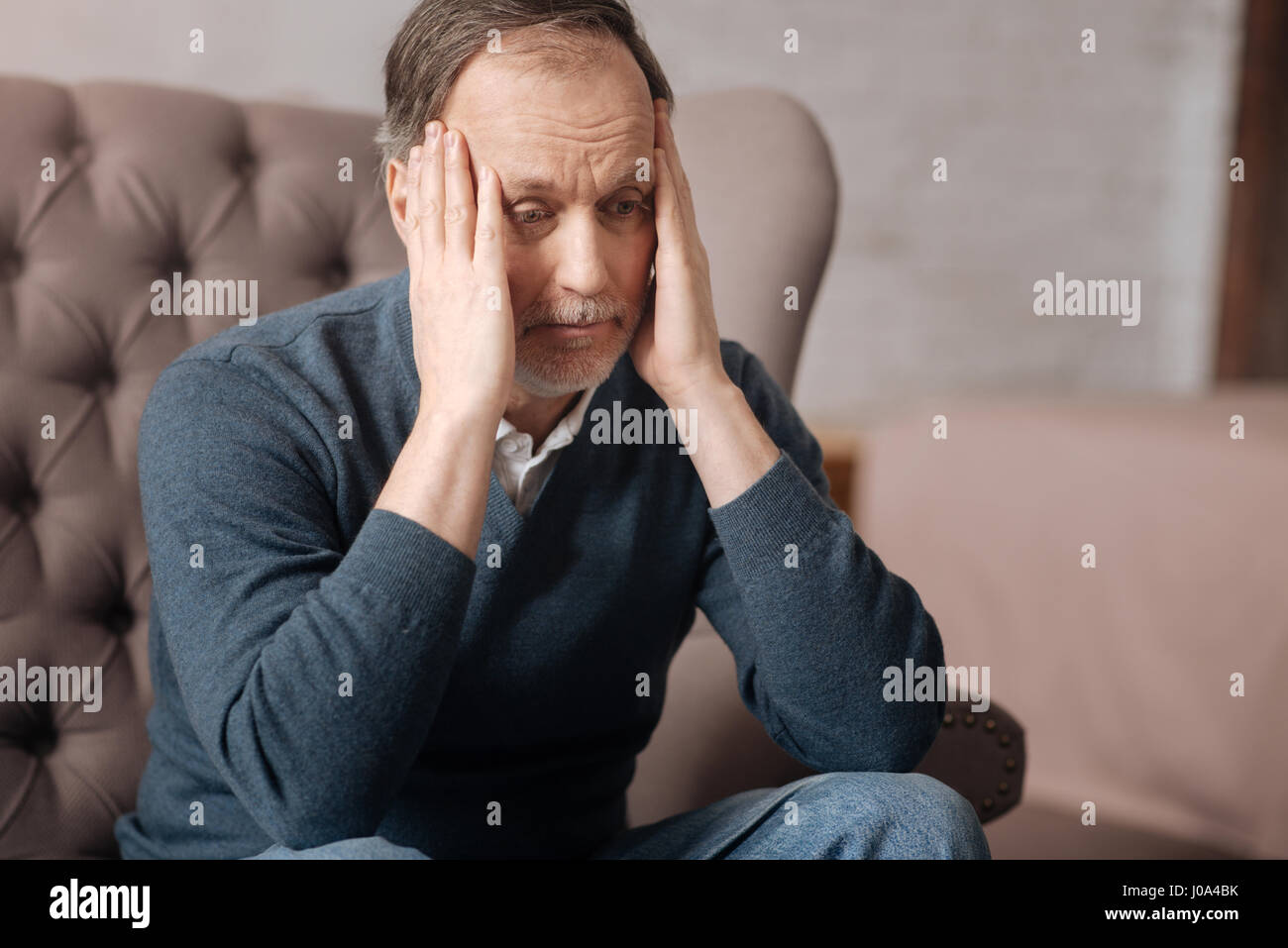 What is happened. Close up of frustrated senior man sitting on couch and touching his temples with hands. - Stock Image