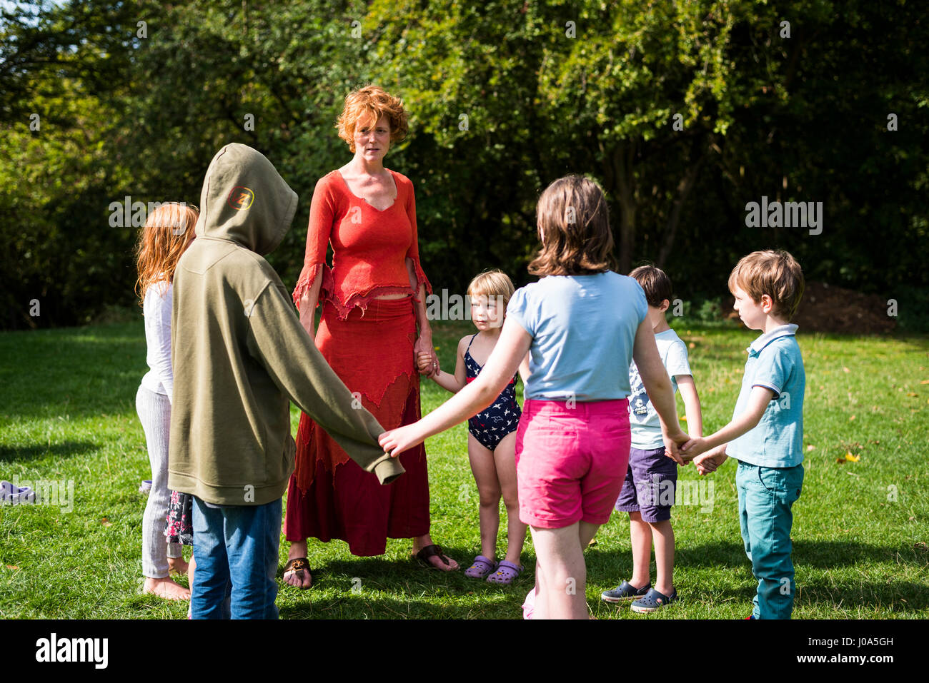 Woman leading a drama workshop for children at a summer festival - Stock Image