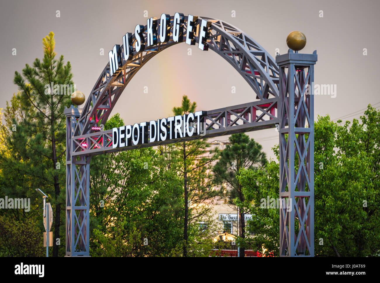 Rainbow touching down behind the gateway arch at Muskogee, Oklahoma's Depot District, home of the Oklahoma Music Stock Photo