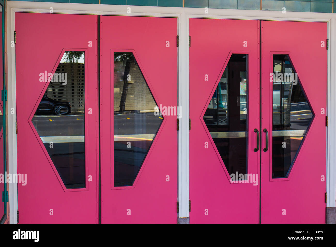 Bright Pink Doors With Glass Window Cutouts - Stock Image