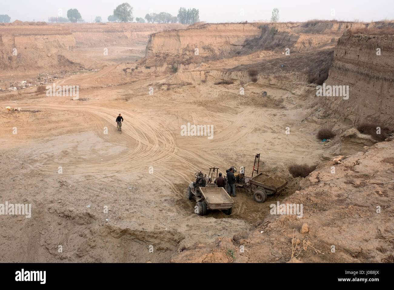 Men dredge earth or sand in a huge pit in Xiong County, Hebei province, China. 09-Apr-2017 - Stock Image