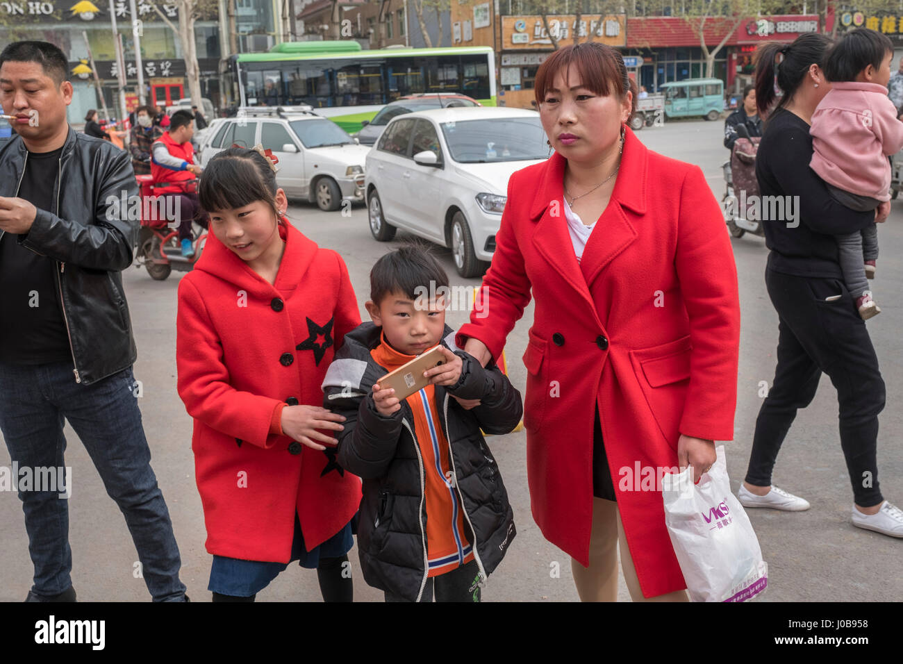 A mother with two children, one girl and one boy, in Xiong County, Hebei province, China. 09-Apr-2017 - Stock Image