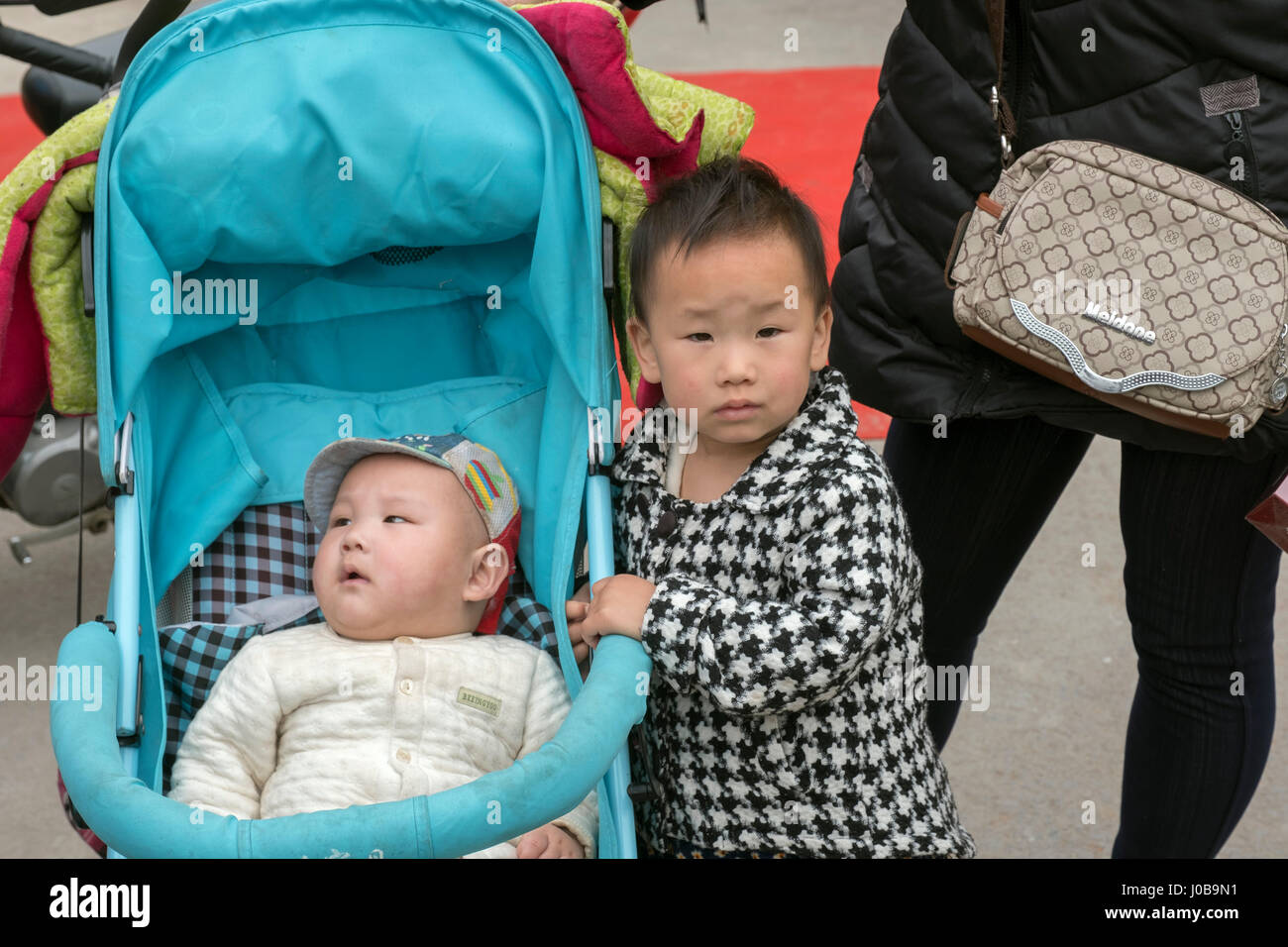 A sister and her new born brother in Xiong County, Baoding, China. China's new two-child policy sparks increase - Stock Image