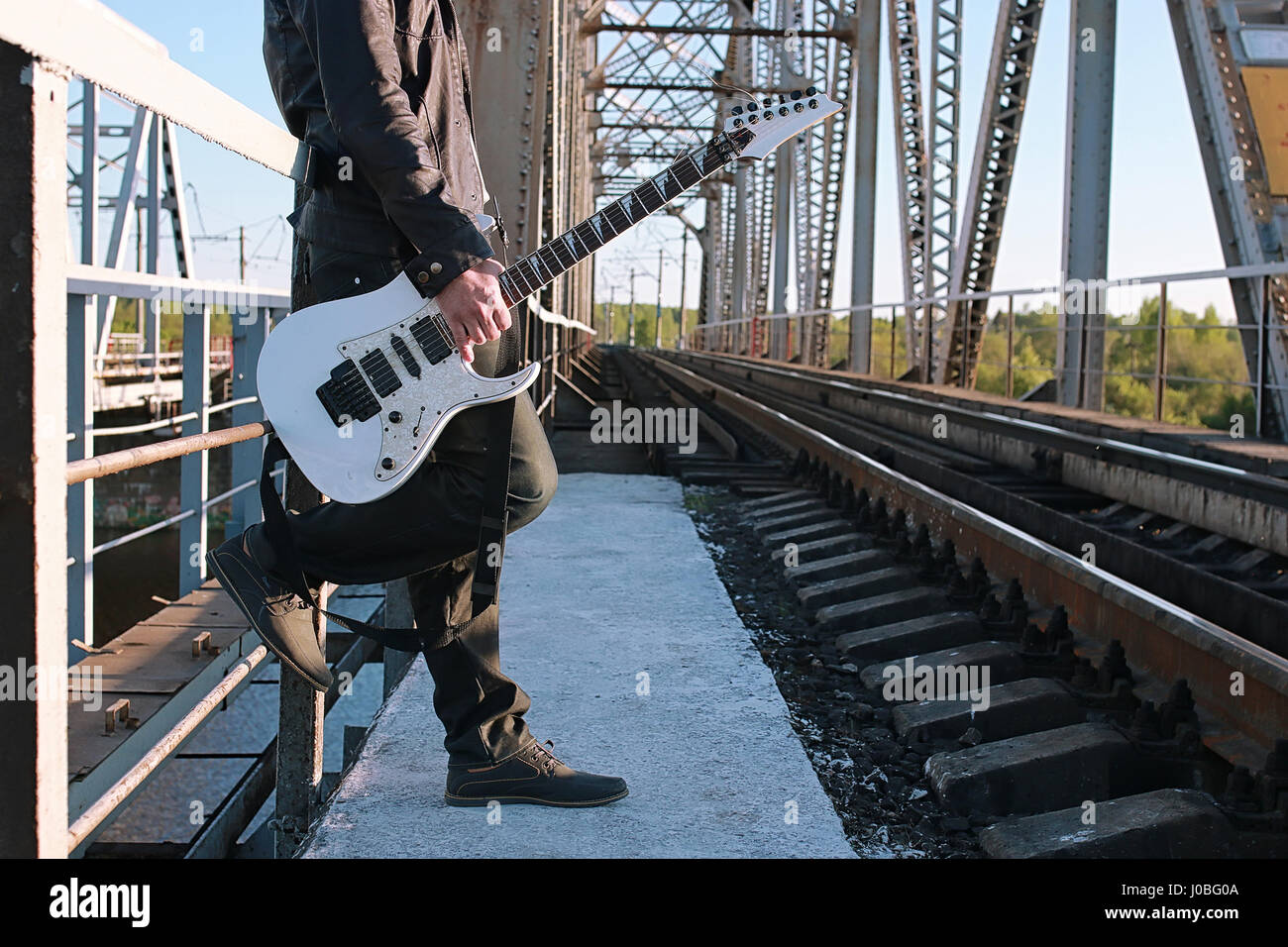 Man with an electric guitar in the industrial landscape outdoors - Stock Image